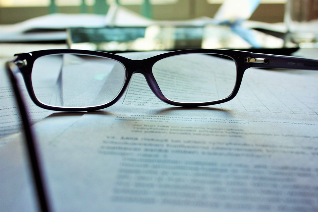 A pair of glasses on top of paperwork