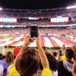 People at football stadium holding up their phones
